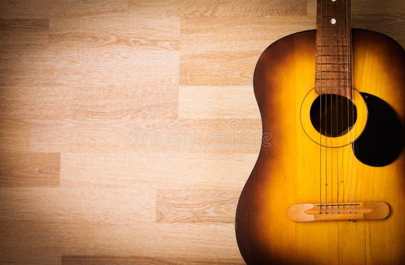 Guitarra acústica que descansa contra um fundo vazio do grunge fotografia de stock royalty free
