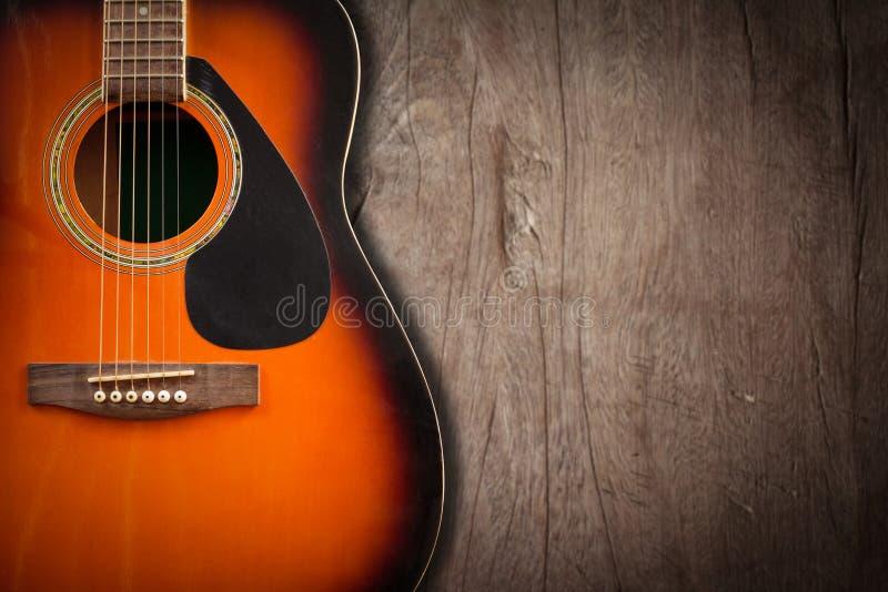 Guitarra acústica que descansa contra um fundo vazio do grunge com c foto de stock royalty free