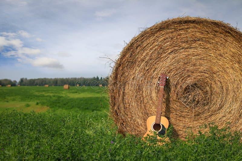 Guitarra acústica que pone contra una bala de heno imagenes de archivo
