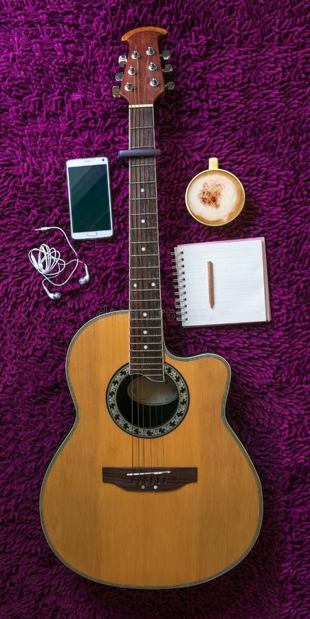 Guitarra acústica, smartphone, taza de café y cuaderno en blanco foto de archivo libre de regalías
