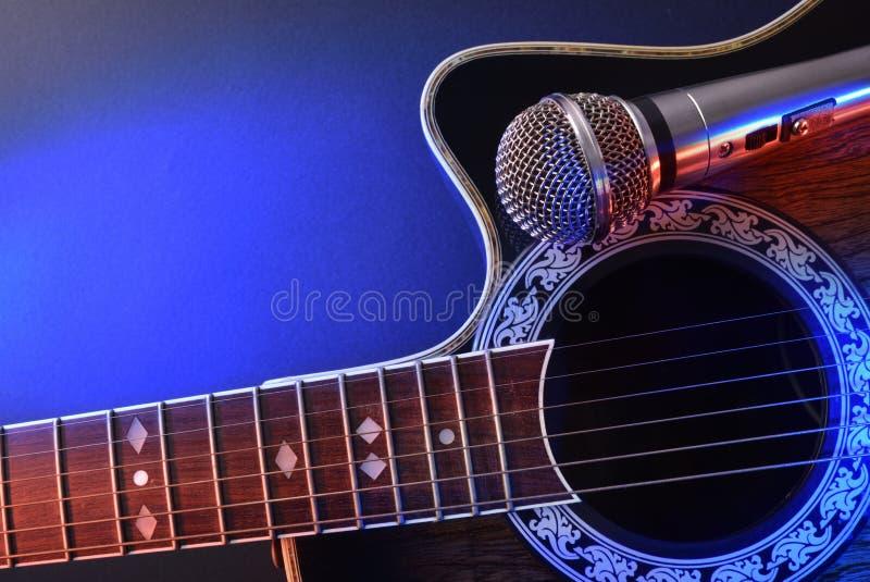 Guitarra acústica y micrófono aislados con las luces rojas y azules foto de archivo