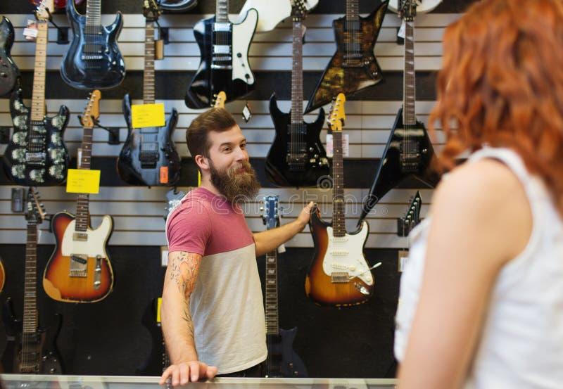 Guitarra auxiliar del cliente que muestra en la tienda de la música imagen de archivo libre de regalías