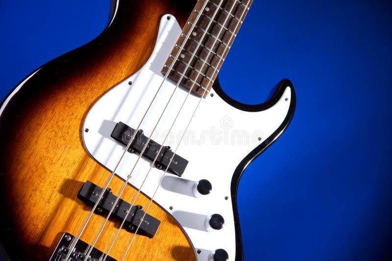 Guitarra baixa no azul fotografia de stock royalty free
