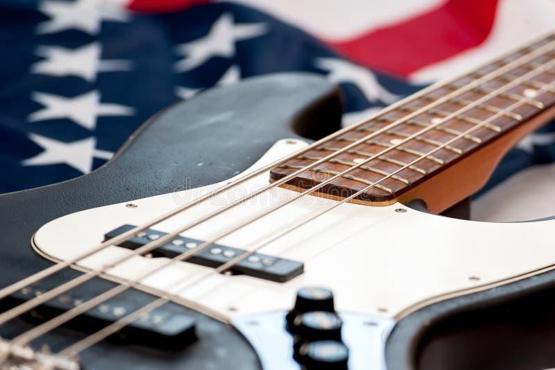 Guitarra-baixo do vintage no fundo da bandeira americana foto de stock