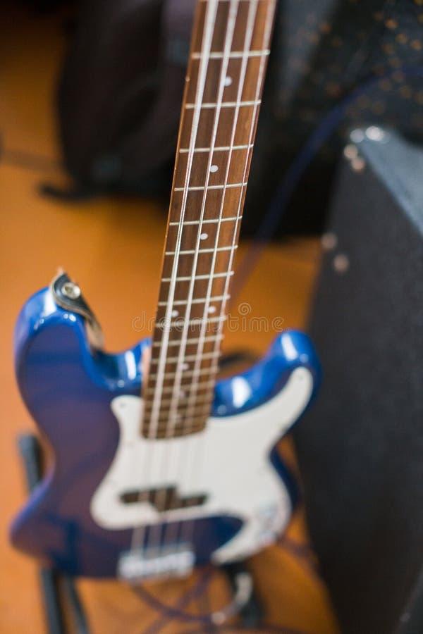 Guitarra-baixo elétrica azul no assoalho fotografia de stock