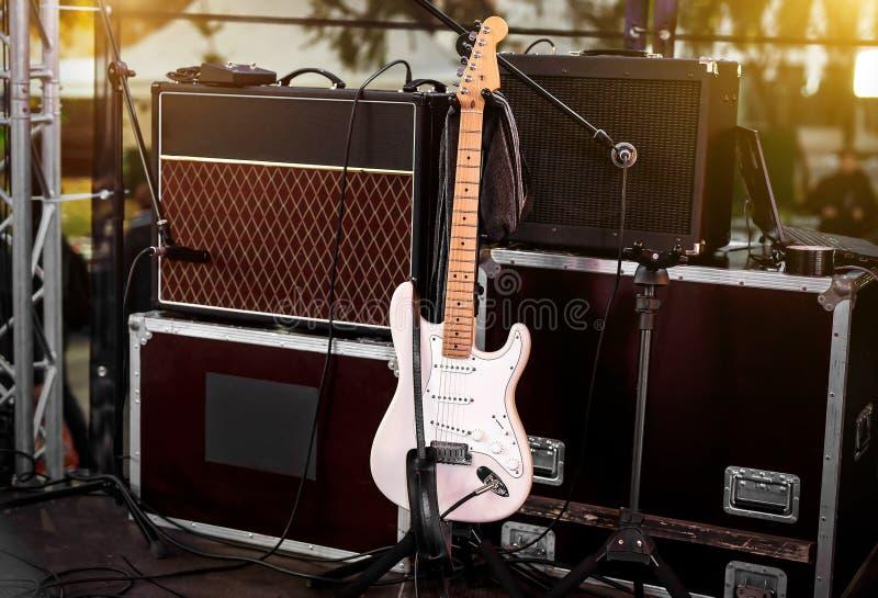 Guitarra blanca en etapa entre los amplificadores y el otro equipo musical imagenes de archivo