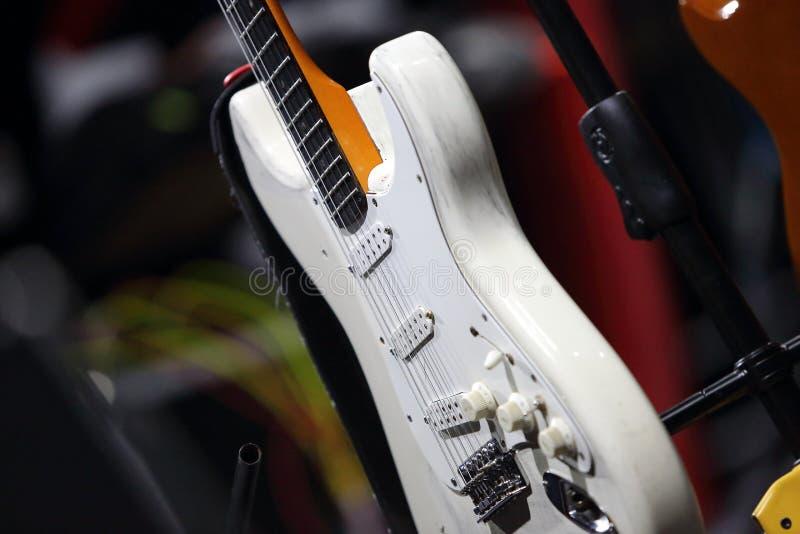 Guitarra blanca a solas en el soporte antes del concierto fotografía de archivo libre de regalías