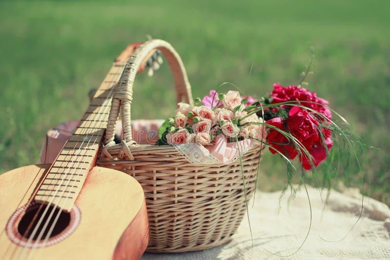 Guitarra, cesta y ramo de flores Fondo blando del vintage fotos de archivo libres de regalías