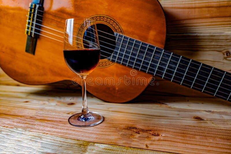 Guitarra clássica velha no fundo de madeira e em um vidro do vinho foto de stock royalty free