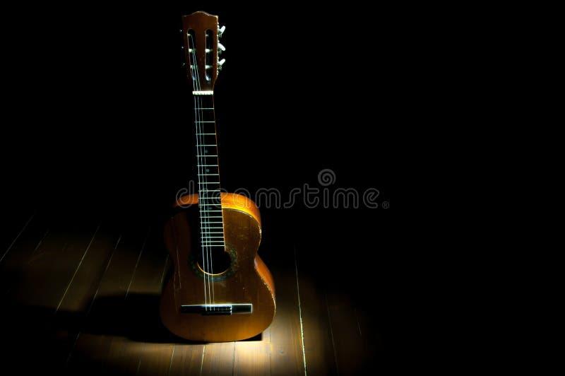 Guitarra clássica velha, vestida no assoalho fotografia de stock