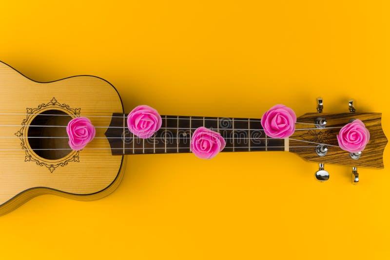 guitarra con las flores color de rosa en las mentiras de las secuencias en fondo amarillo vibrante imagenes de archivo
