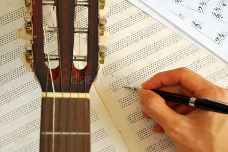 Guitarra con música que compone de la mano en el manuscrito imagenes de archivo