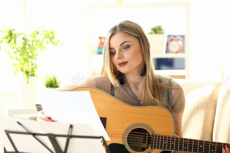 Guitarra da casa que joga o instrumento da posse da menina da lição imagem de stock royalty free