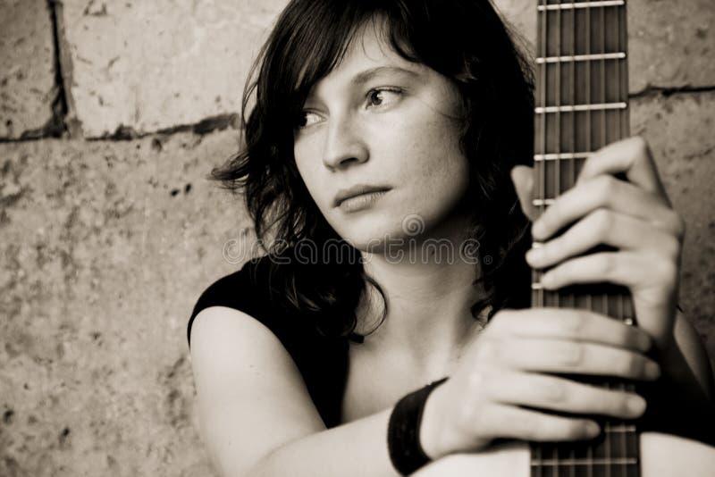 Guitarra da terra arrendada da mulher imagem de stock