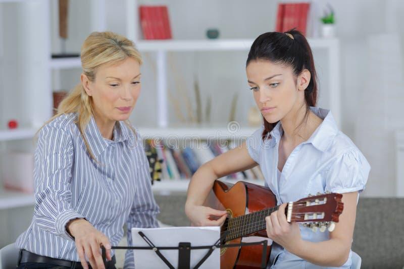 Guitarra de enseñanza del profesor de la música de la señora al estudiante joven foto de archivo