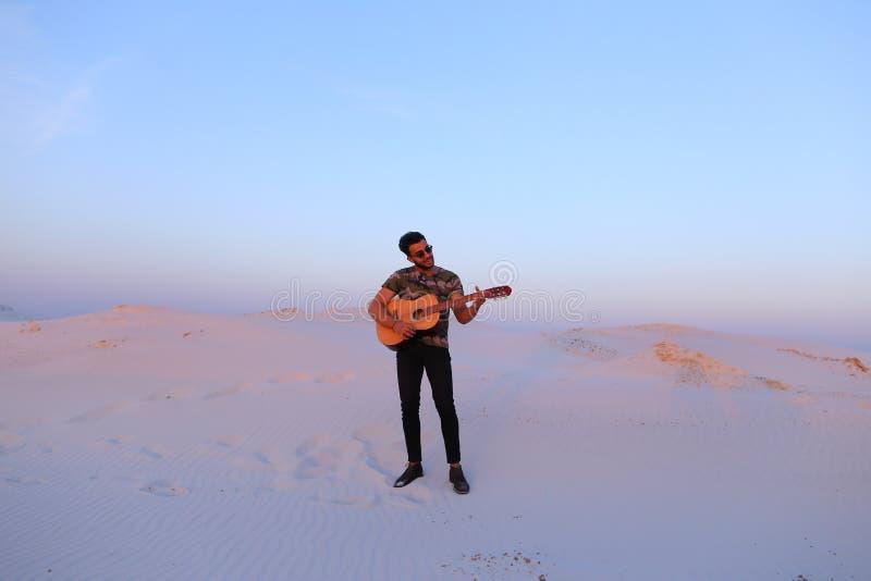 Guitarra de jogo árabe masculina considerável que está no meio do bottomle imagem de stock