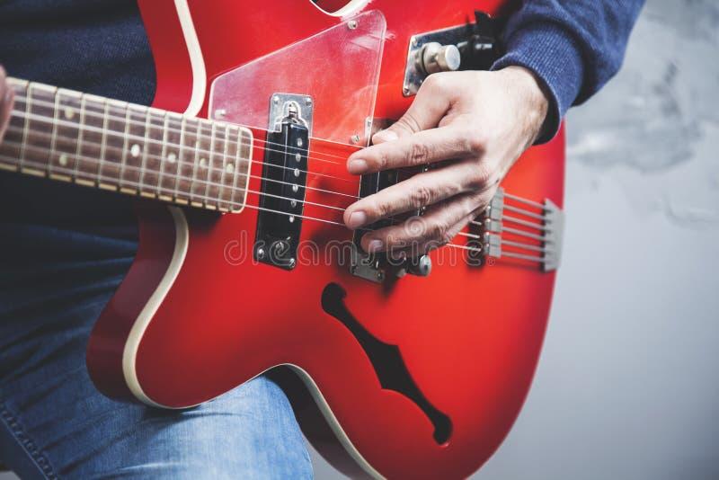 Guitarra de la mano del hombre fotografía de archivo libre de regalías