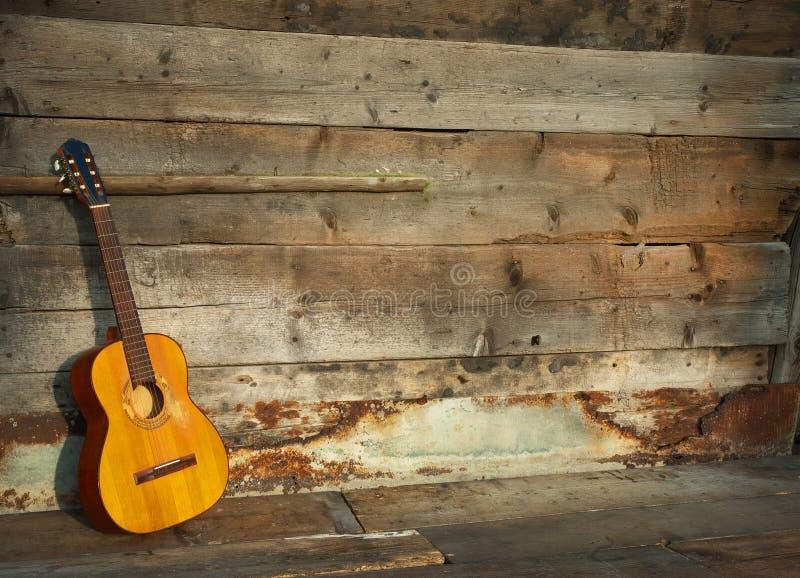 Guitarra de los azules la pared de madera vieja como fondo fotografía de archivo
