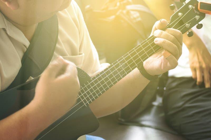 Guitarra de Playing Modern Ukulele do músico profissional no partido imagem de stock