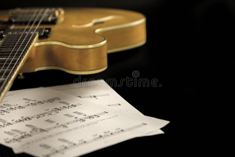 Guitarra del archtop del vintage en la opinión de alto ángulo natural del primer del arce con las hojas de música en fondo negro fotos de archivo libres de regalías