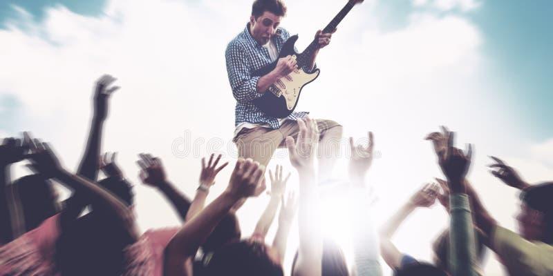 Guitarra del hombre joven que realiza concepto extático de las muchedumbres del concierto imagen de archivo libre de regalías