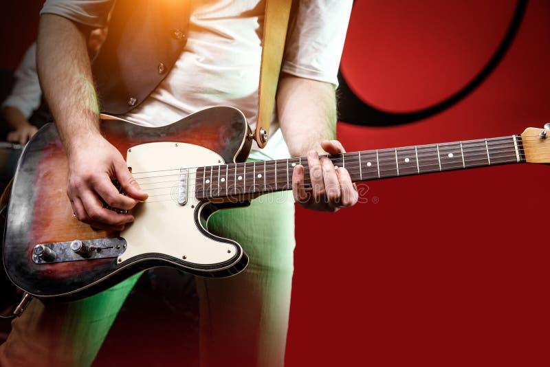 Guitarra del juego de la mano del guitarrista en etapa del concierto con la luz roja imágenes de archivo libres de regalías