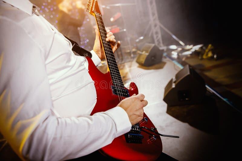 Guitarra del juego de la mano del guitarrista en etapa del concierto con la guitarra roja fotografía de archivo libre de regalías