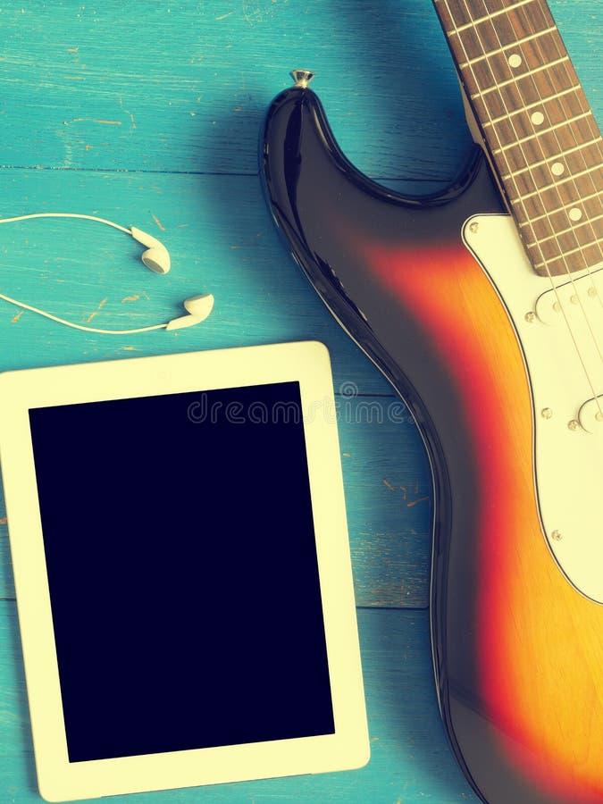 Guitarra del vintage con los auriculares en la madera imagen de archivo