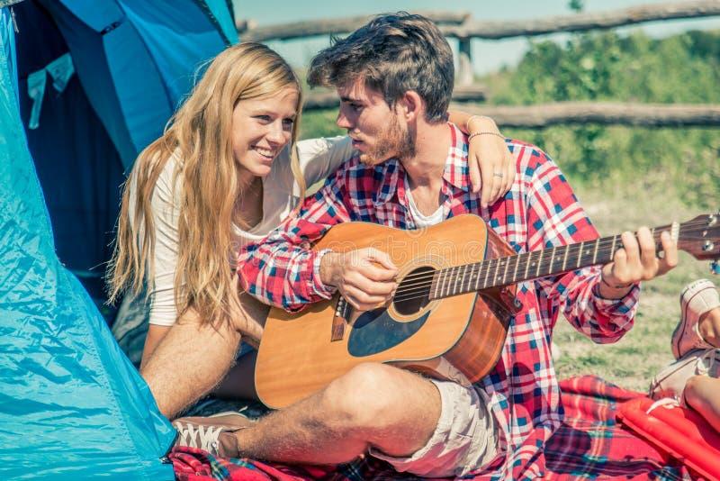 Guitarra do jogo dos pares em um acampamento imagem de stock