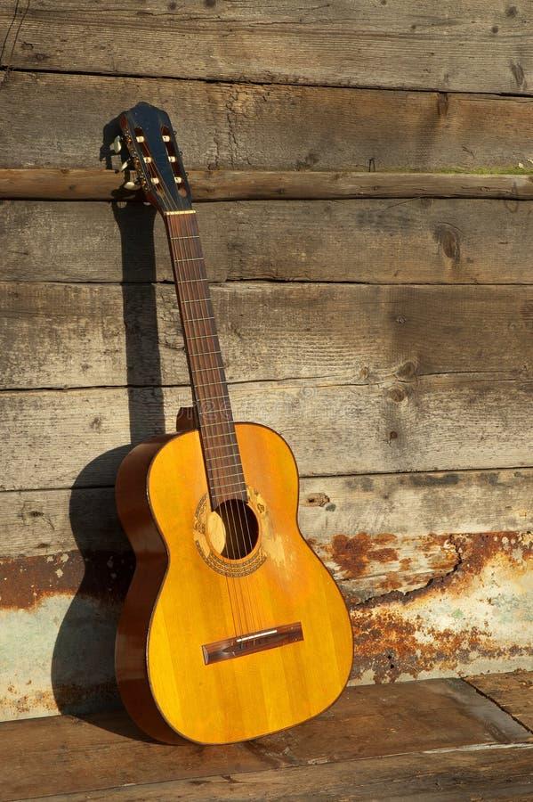 Guitarra dos azuis a parede de madeira velha imagens de stock