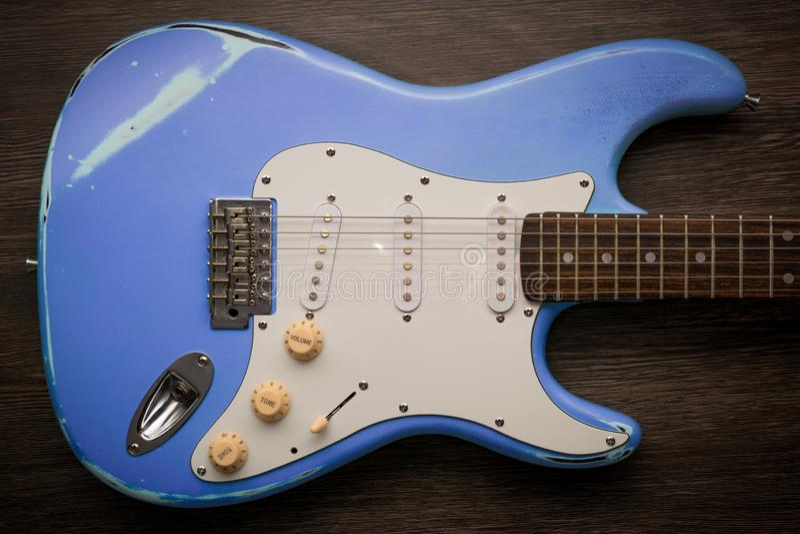 Guitarra eléctrica azul contra fondo de madera marrón Guitarra gastada de la edad del vintage imagen de archivo libre de regalías