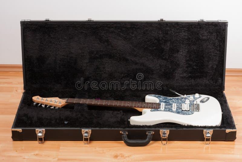 Guitarra el?ctrica blanca en caja de cuero negra imagen de archivo libre de regalías
