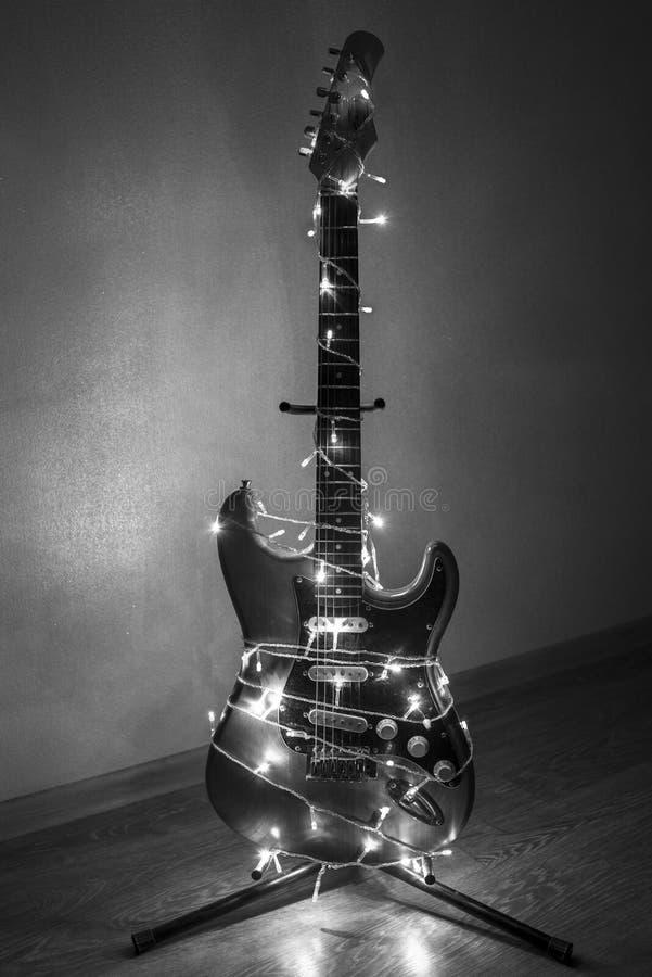 Guitarra eléctrica envuelta en guirnalda colorida, la idea de la música del día de fiesta, foto blanco y negro foto de archivo