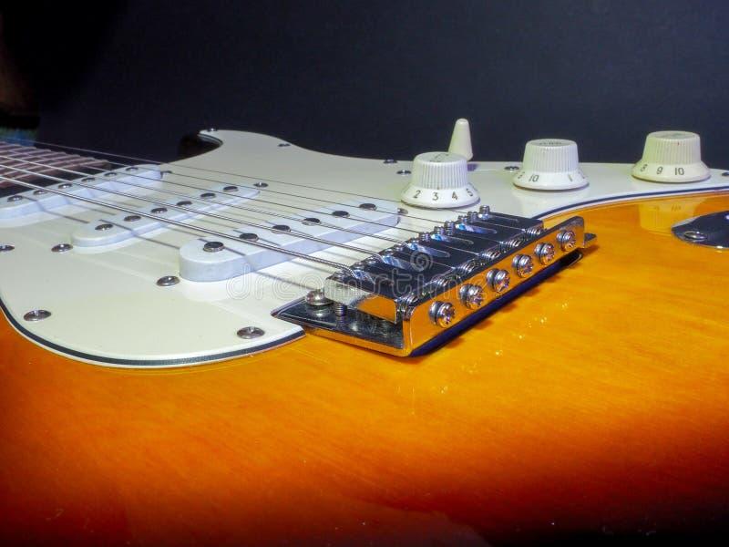 A guitarra elétrica clássica da cor do marrom escuro com branco introduz detalhes do cromo e cordas do ferro foto de stock