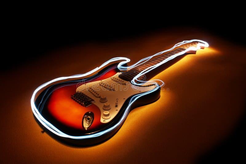 Guitarra elétrica com fulgor da borda em escuro - fundo azul Técnica de Lightpainting fotografia de stock