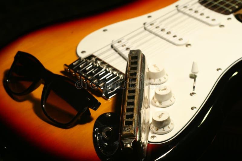 Guitarra elétrica do vintage, harmônica, óculos de sol no fundo preto fotos de stock