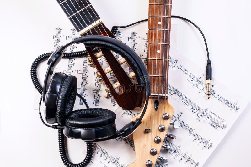 Guitarra elétrica e fones de ouvido com notas da música imagens de stock royalty free