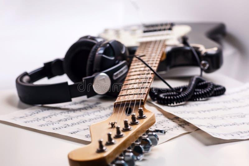 Guitarra elétrica e fones de ouvido com notas da música fotografia de stock royalty free