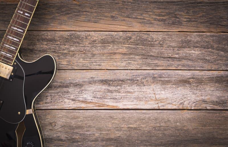 Guitarra elétrica preta em um fundo de madeira rústico foto de stock royalty free