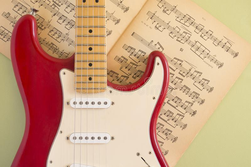 Guitarra elétrica que encontra-se em um fundo colorido e iluminada pela luz natural fotos de stock