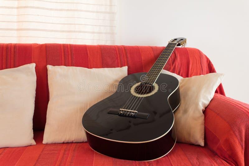 Guitarra en un sofá rojo fotografía de archivo libre de regalías
