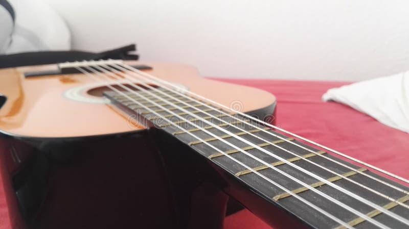 Guitarra en una hoja roja imagenes de archivo