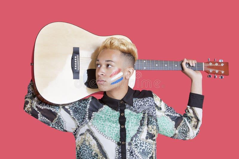 Guitarra levando do adolescente com a bandeira holandesa em sua cara sobre o fundo cor-de-rosa fotografia de stock royalty free