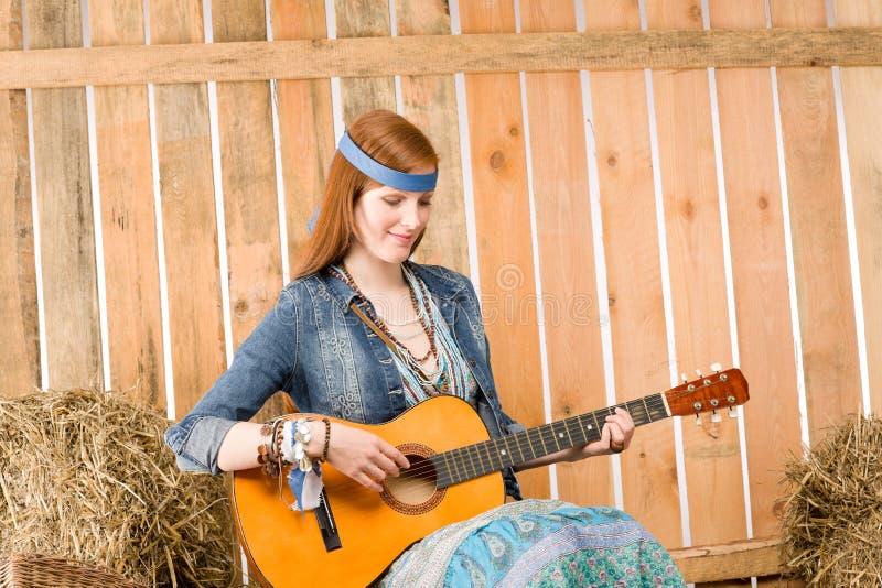 Guitarra nova do jogo da mulher do hippie no celeiro foto de stock royalty free