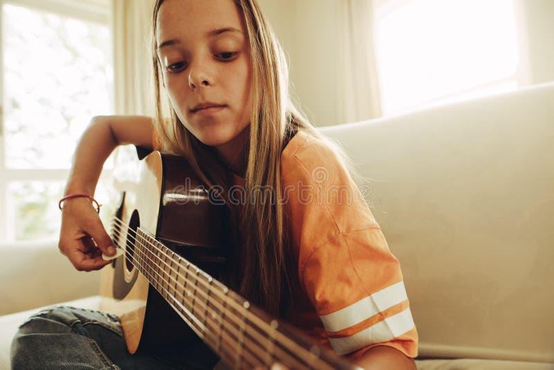 Guitarra praticando da menina em casa imagens de stock