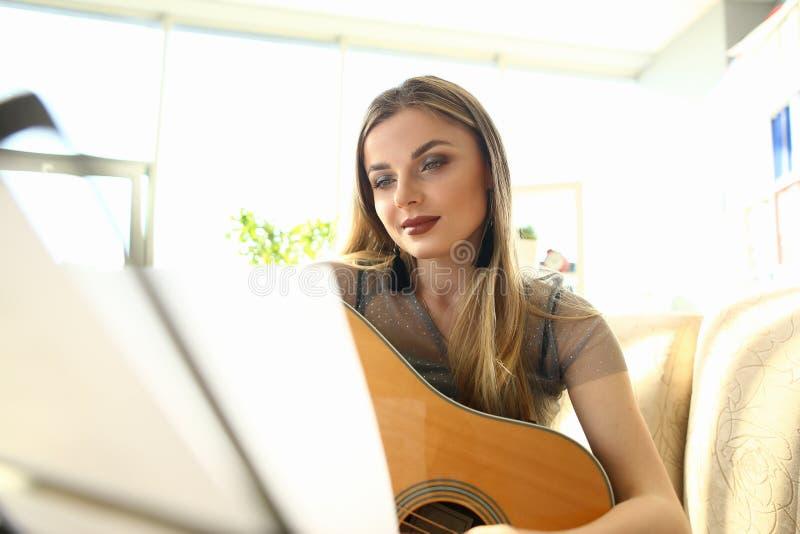 Guitarra que joga o instrumento bonito da posse da menina da lição foto de stock royalty free