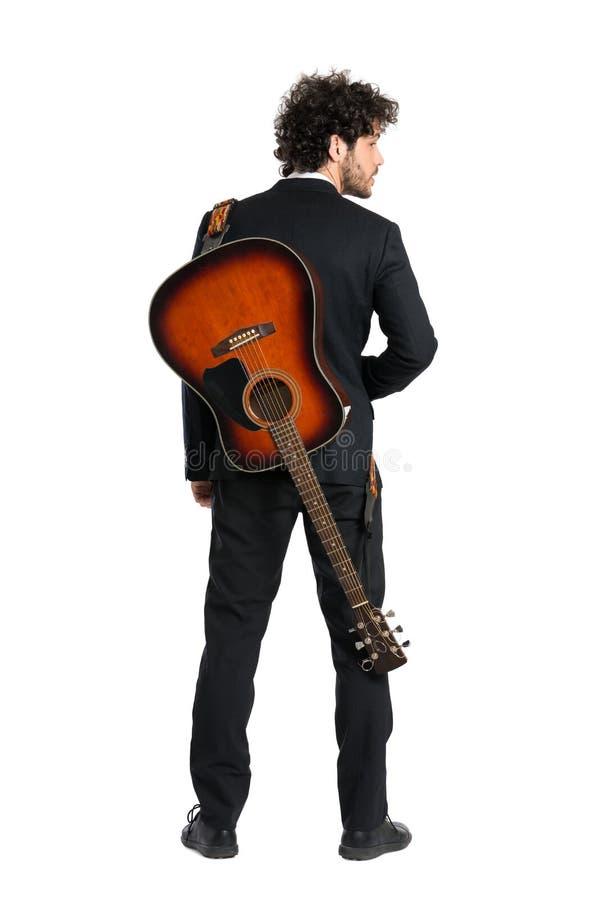 Guitarra que lleva del hombre joven fotografía de archivo libre de regalías