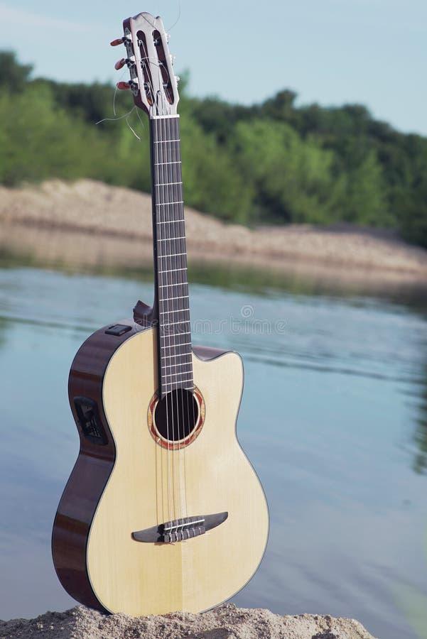 guitarra que se coloca solamente en la arena imágenes de archivo libres de regalías
