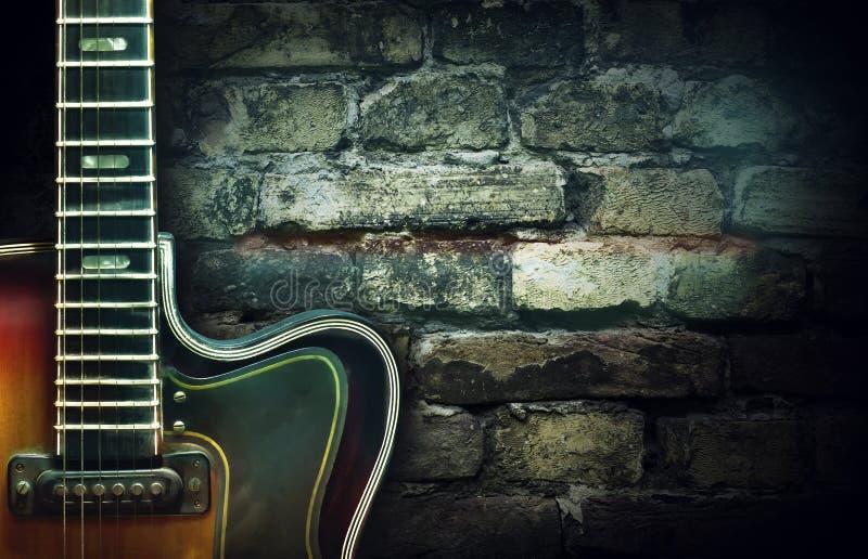 Guitarra vieja del jazz del vintage en un fondo de la pared de ladrillo Copie el espacio Fondo para los conciertos, festivales, e imagen de archivo libre de regalías