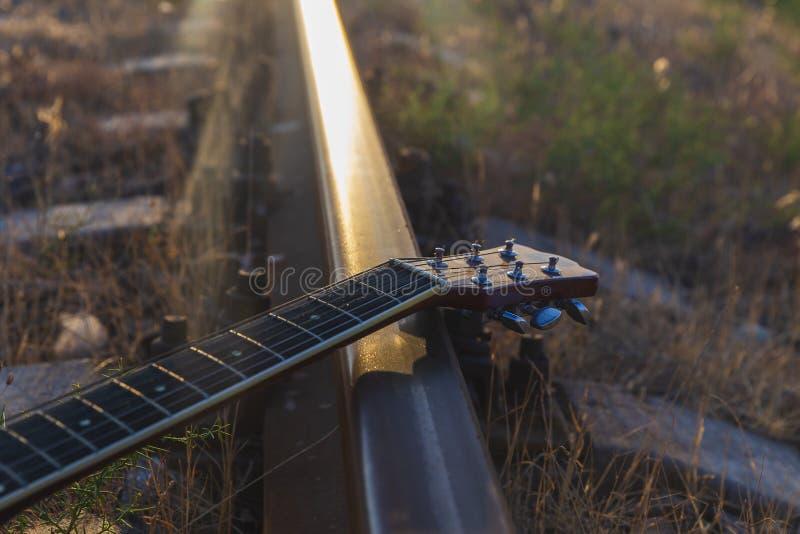 Guitarra vieja que miente en los carriles fotos de archivo